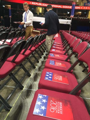Republican National Convention workers place the GOP platform on each delegate chair on the floor of the Quicken Loans Arena on Monday.