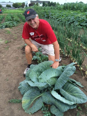 Warren Jahns of Fond du Lac shows off an enormous cabbage he grew at Fond du Lac's Community Garden, located at the corner of Grove Street and Pioneer Road.