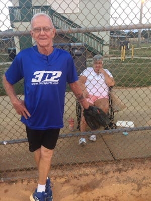 Alton Apsley, 78, stands in front of the fence while his biggest fan, his wife Grace, looks on.