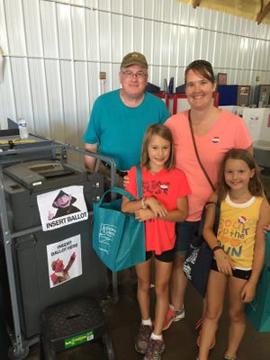 Bill Waldie with record-breaking voters Melanie Safly, Paige Safly, 10, and Alaina Safly, 8, of North Liberty. The trio voted together at the Johnson County Fair Mock Election Thursday, and helped break the record for votes cast in the mock election.