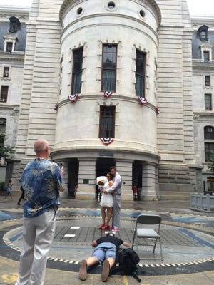 Anikka and Rocco Rounbehler were lucky for the wedding day rain that pushed protesters out of the City Hall courtyard in time for their photos.