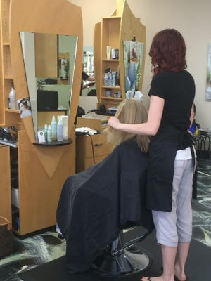 A stylist at the Sage Tree Salon and Day Spa's Altoona location works on a customer's hair. The salon uses Aveda products at its downtown Des Moines and Altoona locations.