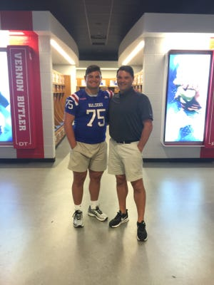 Oak Grove offensive lineman Joshua Mote, left, poses for a picture Thursday with his father, Mike, a former Tech offensive lineman. Mote committed to the Bulldogs on Thursday during a visit.