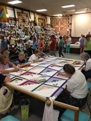 In the quilting barn at the Kutztown Folk Festival, over 2,000 local handmade quilts were on display and for sale, and women participated in a quilting bee.