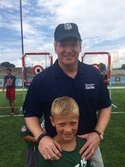 """Brett Rybarczyk, 8, of Cleveland, poses with NFL Commissioner Roger Goodell during the Pro Football Hall of Fame's """"First Play"""" event in Canton, Ohio."""