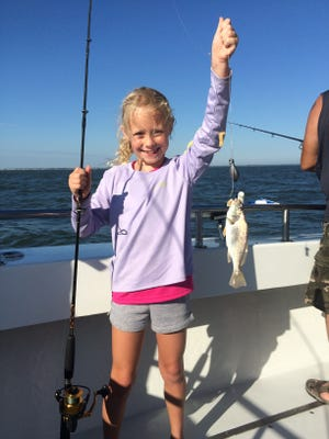 Seven-year-old Madison Wyant proudly shows off her croaker.