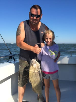 With some help from her uncle Bud Wyant, 7-year-old Madison Wyant shows off her drum fish.