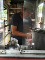 David Stoll, owner of Boo-kie's, grills burgers and chicken Monday at his Church Street food cart.
