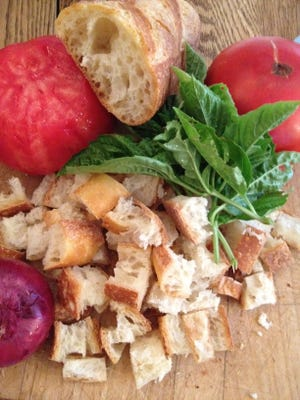 Panzanella, Italian bread salad, is a perfect dish for a hot August night. Local tomatoes, cucumber, onion and garlic are tossed with a base of a torn-up locally made baguette. No cooking required!
