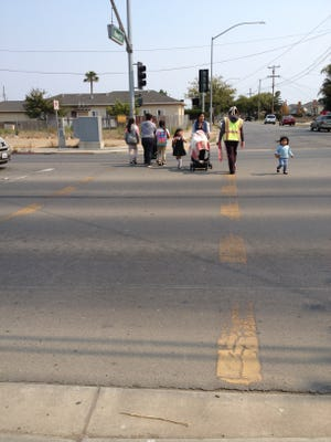 Parents and children cross the street toward Martin Luther King Jr. Academy on Friday afternoon. The crosswalk is nearly worn out completely.