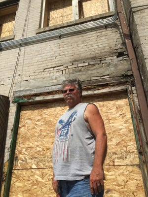 Gary Mulheron stands outside his business, A to Z Wholesale, 2233 W. Fond du Lac Ave., which was set afire during last weekend's riot.