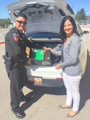 Santa Clara police officer Jaime Serrano distributed school supplies to Central Elementary on Friday with principal Margaret Kesler receiving the items.
