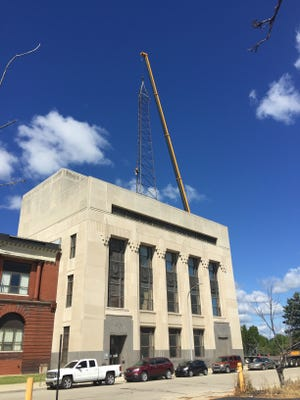A crane is positioned Monday morning to work at removing a tower on top of the AT&T building in Port Huron.