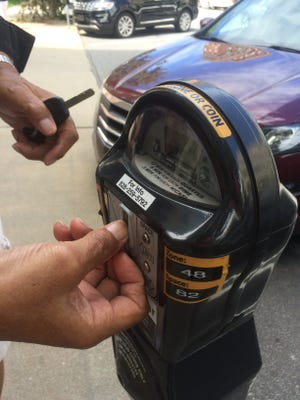The city of Asheville is lowering many of its meters to comply with requirements of the Americans with Disabilities Act.