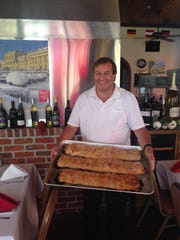 Owner Helmut Heiss holds a pan of apple strudel at