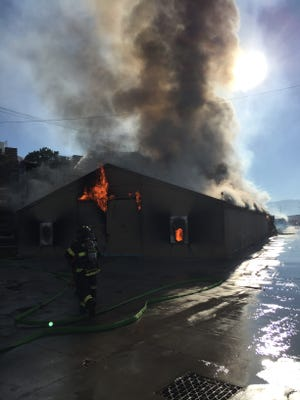 Firefighters battle a structure fire in a Monterey Mushrooms warehouse.