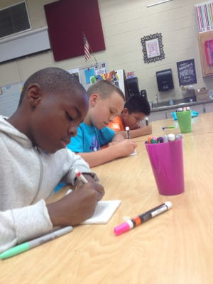 From left, Bradley sixth graders Zachery Marable, Ty Goins and Jose Ortiz, write inspiring messages on tiles,