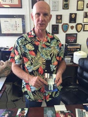 Karate teacher Bob Allen holds a photo of his son Gregory's