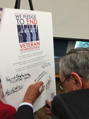 Ron Borgesser, CEO of Oakland Livingston Human Service Agency, signs the pledge to end veteran homelessness