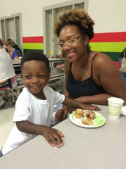Mom Camesha Reynolds visits with other parents and son Jalen, 3, a preschooler with older siblings in first and second grades at P.D. Graham.