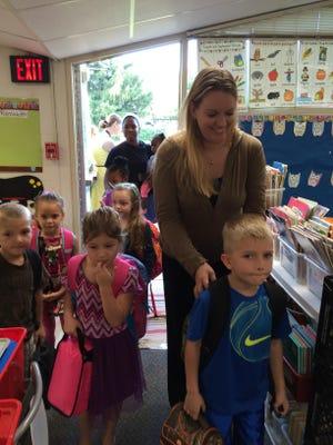 Mom Kari McWhirter escorts son Gunner, 5, into Sandi Stuhr's kindergarten classroom, with kindergarten classmate Abby Isaacson at Kari McWhirter's right side.