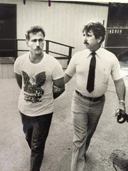 Gary Bennett in a 1983 photo being led away by Palm Bay Police Detective Gus Williams.