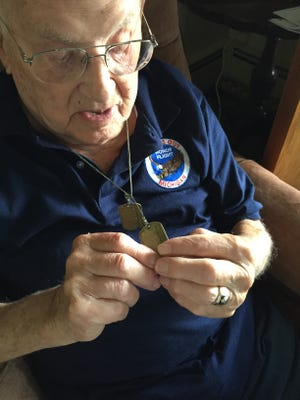 Earl Boman of Lakeport holds his dog tags from World War II.