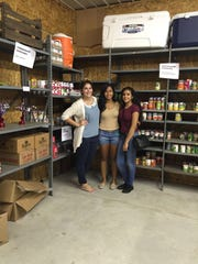 (From left) Jackie Martinez, annual giving director at the YMCA of Vineland, and YMCA members Astry Lopez and Caroline Fernandez, shown in Impact Harvest's storage area, were among volunteers who participated in the YMCA's Togetherhood project. It provided the food bank with 348 pounds of food.