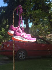 The running shoes of Ally Brueger hang in the front