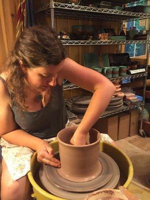 Sarah Vekasi, owner of Sarah Sunshine Pottery, works in her studio creating her unique pottery.