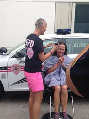 Janet Palmer gets her head shaved by fellow police Officer Kim Bailey.