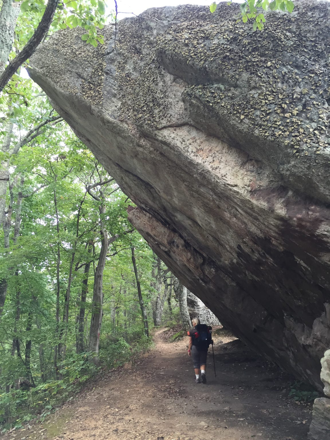 A hiker is dwarfed by a massive rock jutting over the