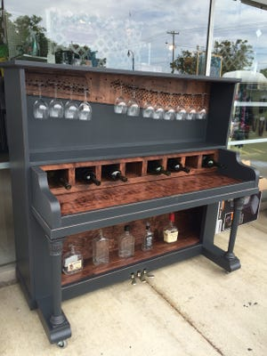 In addition to making wall art, Urban Upcyclers turned an old piano into a bar. The piece sold and buisness is preparing to make another.