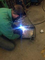 Sparks fly as Dover High School senior Matt Hillyer welds a tray for a class project. Hillyer plans to attend a four-year welding engineering program after high school.