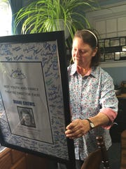 Diane Crews reads a message from her DreamWrights family on the back of a poster presented to her at a retirement party. Crews, who retired from DreamWrights after  two decades with the production company, opened Theatre Arts for Everyone, or TAFE, Oct. 1, 2016.