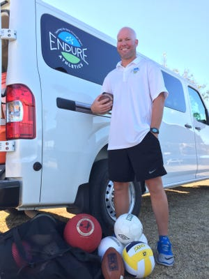 Joel Bigelow with Endure Athletics Club stands in front of the organization's van. The nonprofit provides physical activity and adventures to children in need.