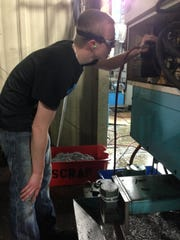 Eighteen-year-old Cody Burke checks fluid levels in a production machine at Gibbs Die Casting Corp.'s Comac machining plant on Ohio Drive. Burke is studying and working toward becoming an apprentice maintenance technician, responsible for maintaining machinery and various electrical, mechanical, hydraulic and other systems.