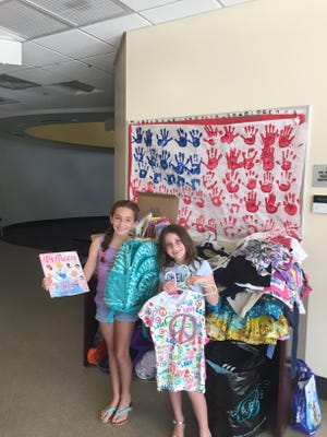Shaina and Sadie Lee with clothing they collected and Donated to the Boys & Girls Clubs of St. Lucie County.