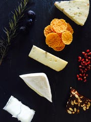 This holiday cheese board includes Cypress Grove's Humboldt Fog (from left), Robiola, Moliterno with Truffles, Wausome Wafers (Clever Cheddar), Carr Valley Glacier Wildfire Blue. It is garnished with a sprig of fresh rosemary and dried figs (left) and pomegranate arils and Savory Spoon Panforte (right).