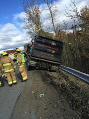 A dump truck teeters on the edge of Interstate 89 north