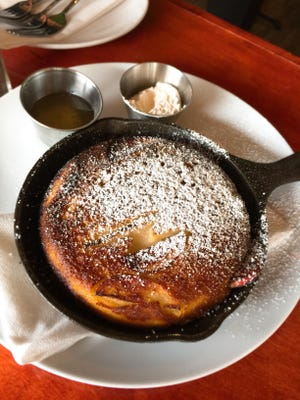 A Dutch Baby pancake, with sliced, caramelized apples folded into the batter, is baked in a cast iron skillet.