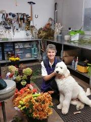 Theresa Clower and her golden doodle Jeff in her flower arranging studio.