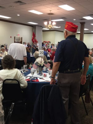 Veterans of the U.S. Marine Corps stand to be honored at a luncheon Friday at Heritage Hall Senior Center.