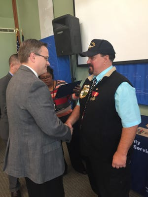 Machinist Mate 3rd Class William Gannon shakes hands with Dale Borchert, chairman of the Dutchess County Board of Legislature, after accepting his medal.
