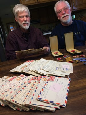 Brothers Griff and Tom Williams sit behind the letters that their father, Don Williams, wrote and two Bronze Stars he earned during World War II.