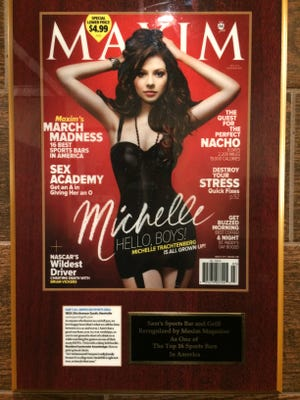 """This framed plaque of a Maxim magazine cover and a small blurb that appeared in the March 2011 issue talk about getting """"chicks"""" hammered so they can be picked up."""