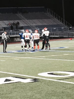 Captains from Union-Endicott and Whitesboro meet at midfield for the coin flip in Friday's Class A state quarterfinal at Cicero-North Syracuse. The Tigers lost, 45-18.