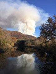 Smoke from a forest fire billows over the Little River on Thursday, Nov. 17, 2016, in Walland.