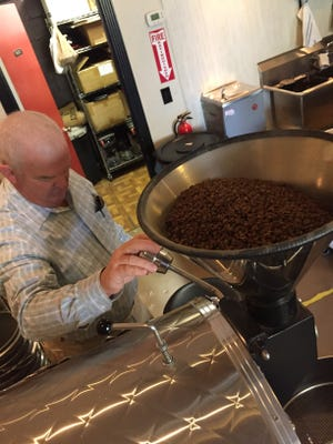 Scott Howard, owner of Portside Java in Hendersonville, checks the temperature of his coffee roaster before starting a small batch in his shop.