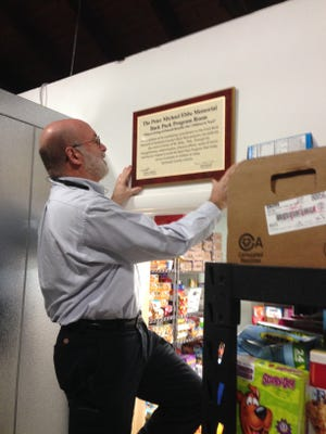 Foodbank Network of Somerset County Board President Gordon White III hangs a plaque honoring Peter Ebbe for his efforts supporting the Foodbank's Backpack Program.